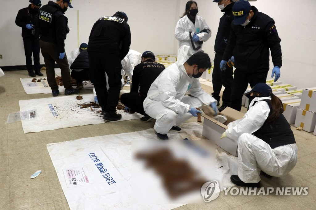 This photo, provided by the May 18 Memorial Foundation, shows researchers examining remains. (PHOTO NOT FOR SALE) (Yonhap)