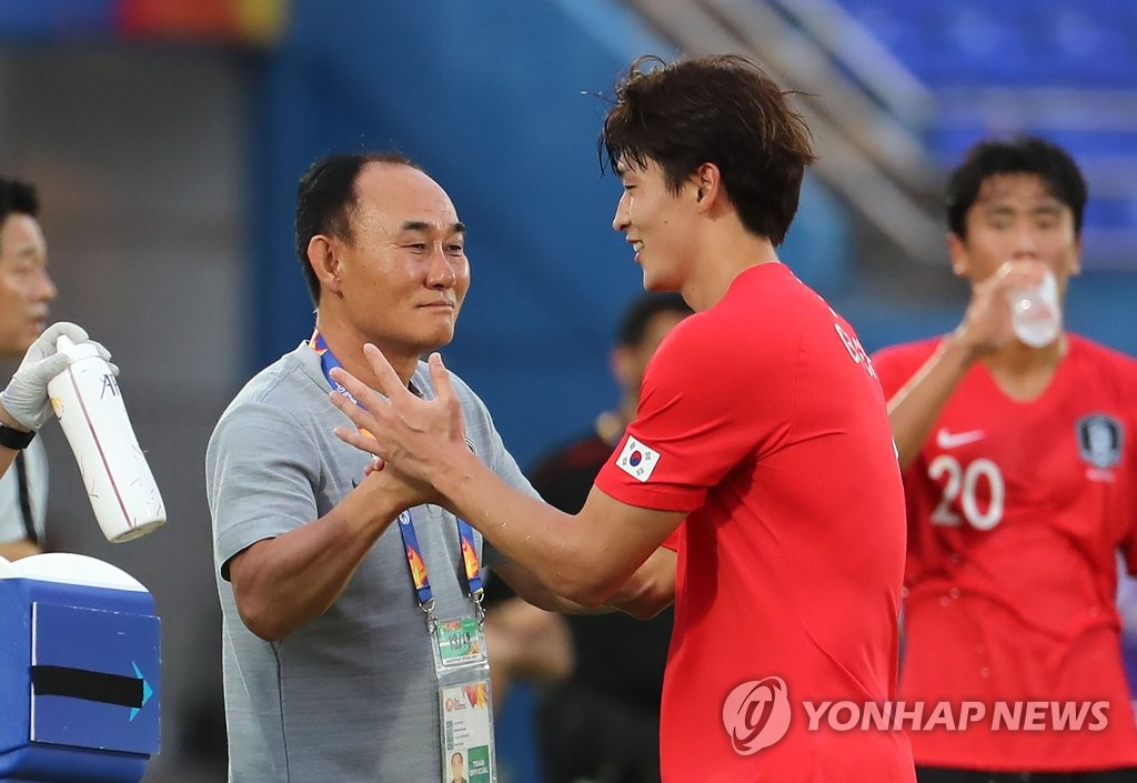 South Korea head coach Kim Hak-bum (L) greets his striker Cho Gue-sung after Cho scored a goal against Iran during the teams' Group C match at the Asian Football Confederation U-23 Championship at Tinsulanon Stadium in Songkhla, Thailand, on Jan. 12, 2020. (Yonhap)