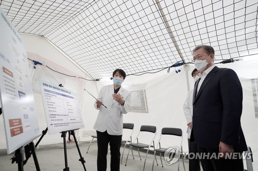 President Moon Jae-in (R) receives a briefing on the National Medical Center's response to the outbreak of a new coronavirus during his visit to the hospital in Seoul on Jan. 28, 2020, in this photo released by Cheong Wa Dae. (PHOTO NOT FOR SALE) (Yonhap)