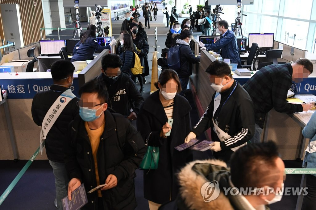 South Koreans and foreigners who flew from China have their body temperatures checked at Incheon International Airport, west of Seoul, on Jan. 28, 2020, as the government is beefing up quarantine efforts to curb the spread of a new coronavirus. (Yonhap)