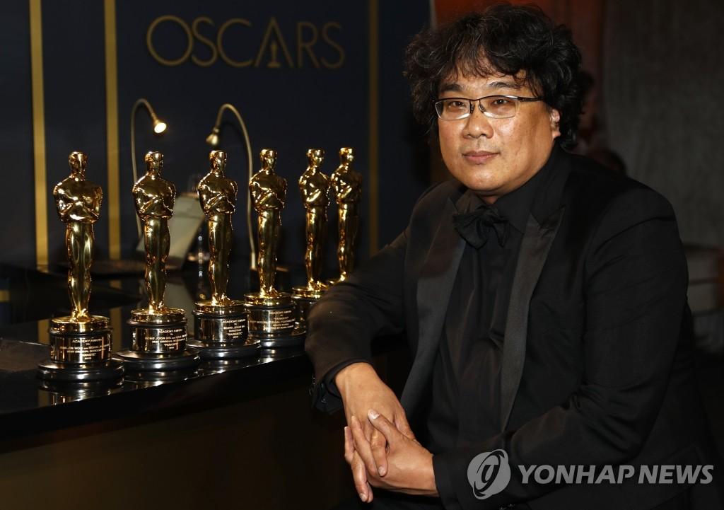 아카데미 트로피와 포즈 취하는 봉준호 감독