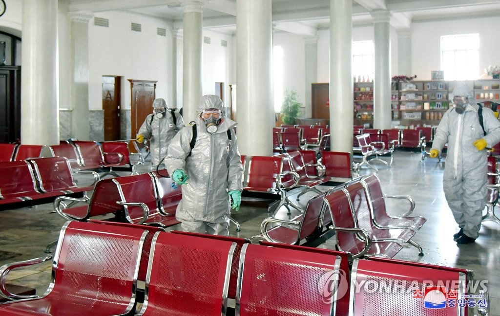 People in protective clothing sterilize an unidentified facility in North Korea to keep the new coronavirus from spreading, in this photo released by the Korea Central News Agency on Feb. 15, 2020. (For Use Only in the Republic of Korea. No Redistribution) (Yonhap)