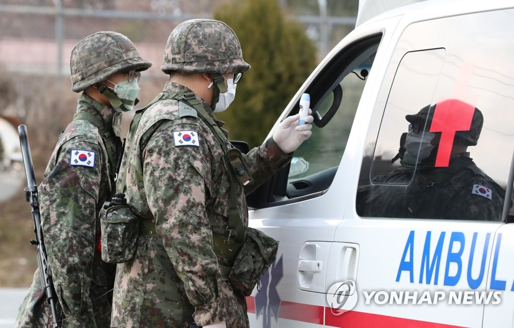 In this file photo, taken on Feb. 26, 2020, troops belonging to the Army's 50th division check the driver of an ambulance for fever near its base in northern Daegu, 300 kilometers southeast of Seoul. (Yonhap)