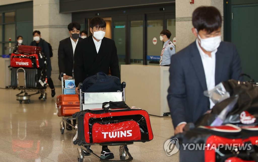 Members of the LG Twins baseball team walk through Incheon International Airport in Incheon, west of Seoul, on March 7, 2020, after returning from their spring training in Japan. (Yonhap)
