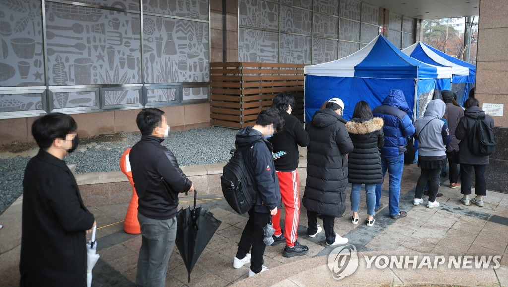 People who work at a building in southwestern Seoul where infections occurred stand in a line to be checked for the new coronavirus on March 10, 2020. (Yonhap)