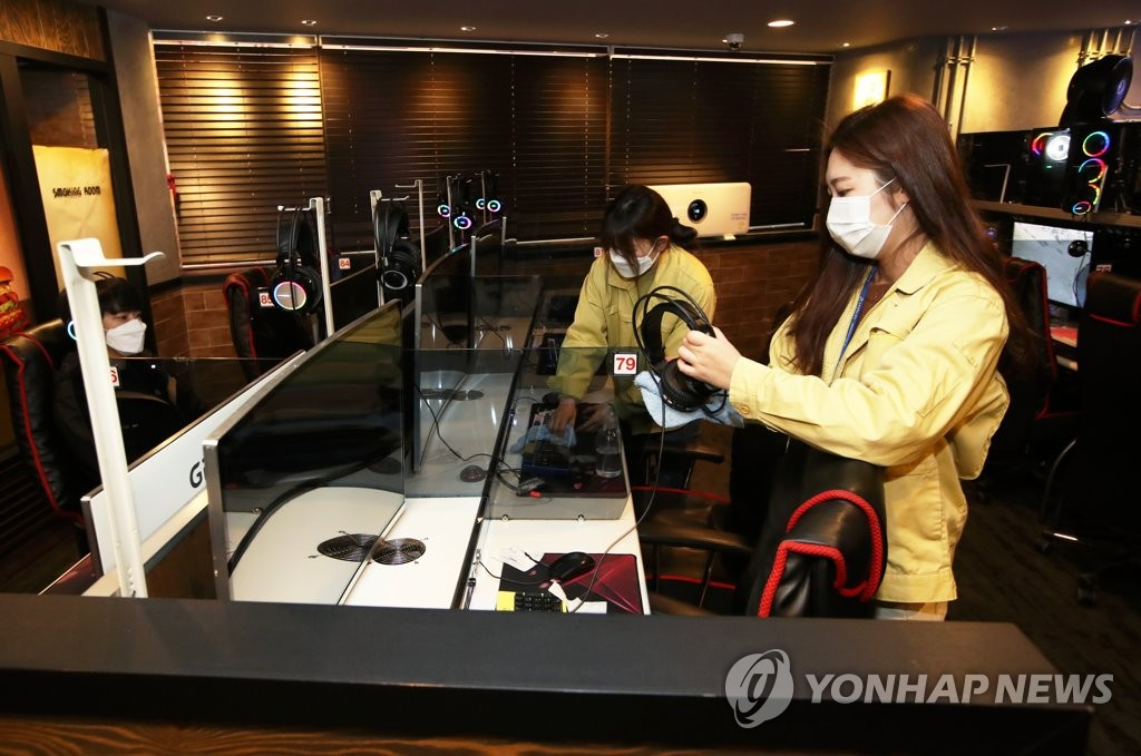 Public officials disinfect computer mice, keyboards and other items at a PC bang, a Korean-style internet cafe, in the southwestern city of Gwangju on March 12, 2020, amid the spread of the new coronavirus. (Yonhap)
