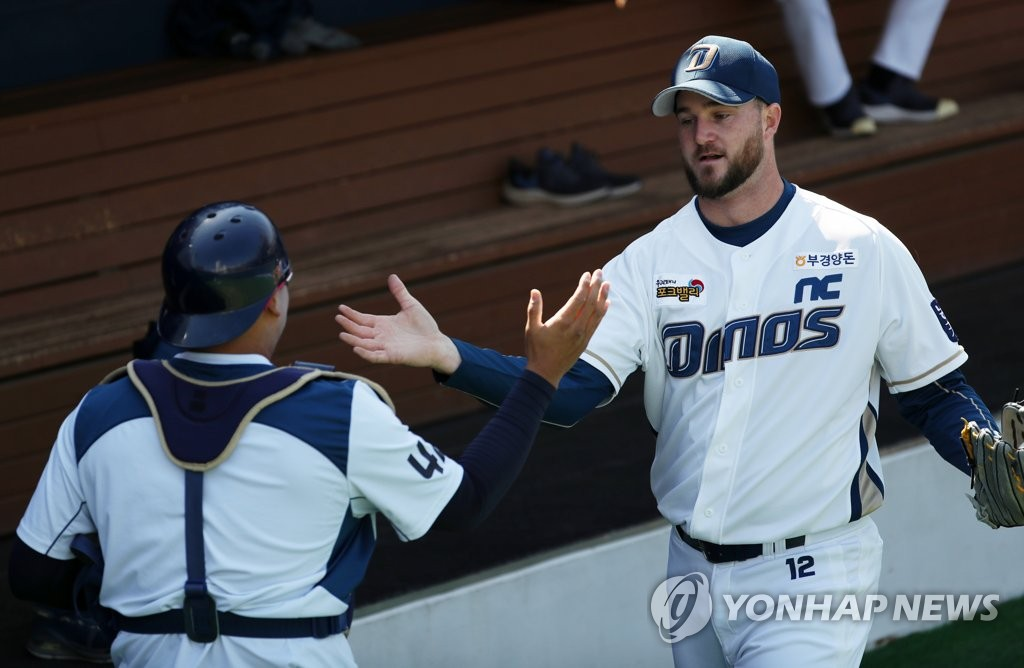 In this file photo from March 16, 2020, Mike Wright of the NC Dinos (R) high-fives his catcher Kim Tae-gun after a bullpen session at Changwon NC Park in Changwon, 400 kilometers southeast of Seoul. (Yonhap)