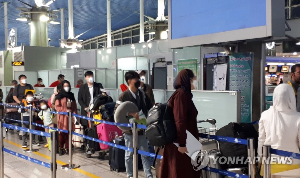South Koreans and their Iranian family members stand in line to go through immigration processes at Imam Khomeini International Airport in Tehran on March 19, 2020, as they were set to return home on chartered flights via Dubai, following a spike in coronavirus infections in the Middle Eastern country. (Yonhap)