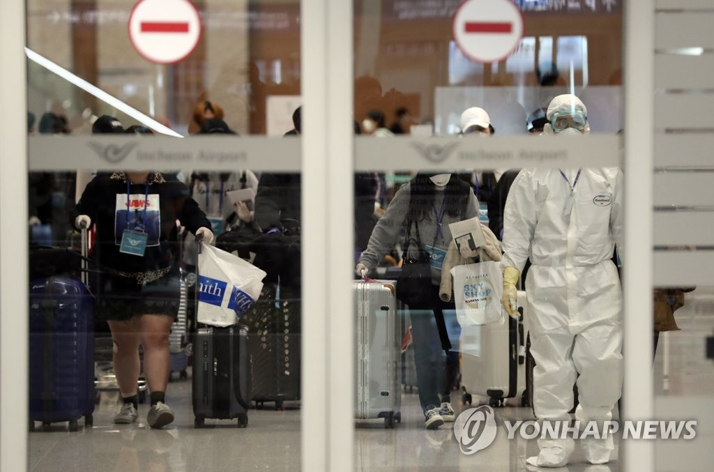 Arrivals with fever and other symptoms at Incheon International Airport, west of Seoul, are escorted by a quarantine worker to a screening station to be tested for COVID-19 on March 27, 2020. (Yonhap)