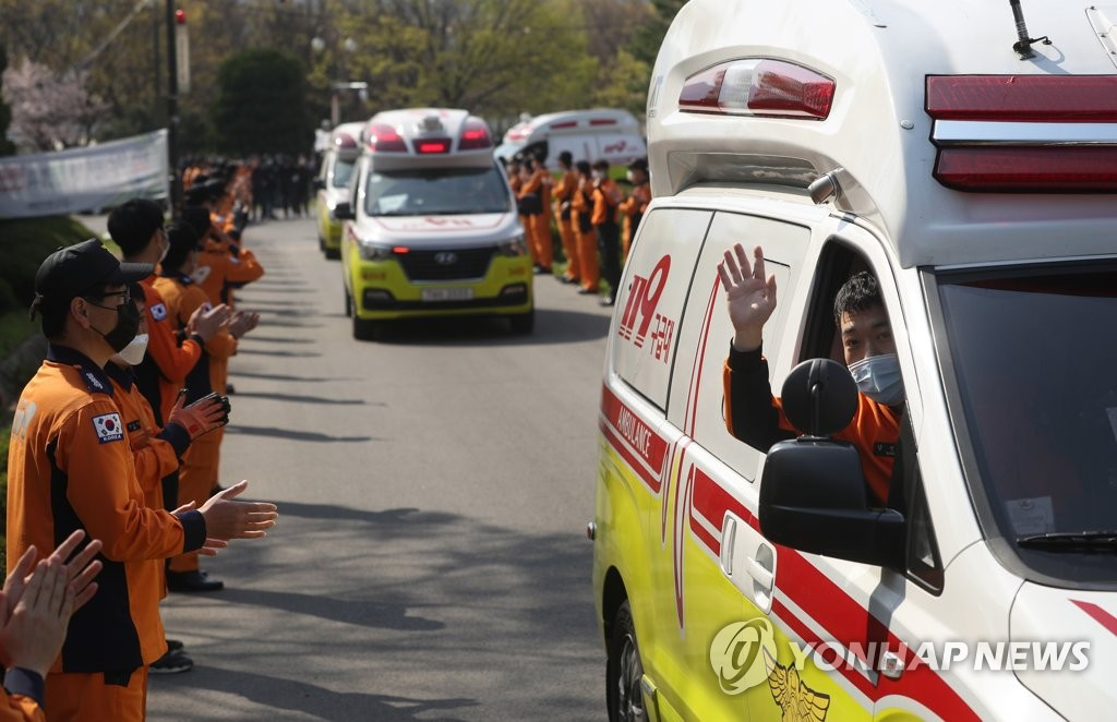 Firefighters and rescue officials gesture to one another as they return to their bases after being mobilized to Daegu to help fight the coronavirus in the city on April 2, 2020. (Yonhap)