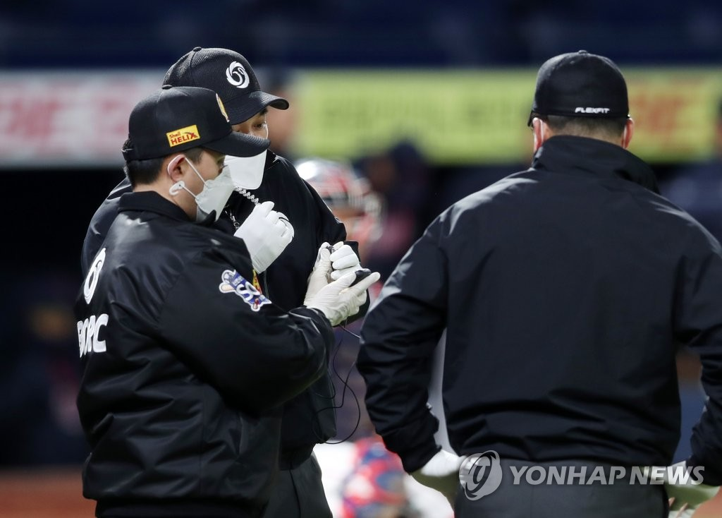 In this file photo from April, 21, 2020, umpires connect with the video replay center at the Korea Baseball Organization head office in Seoul during a preseason game between the Lotte Giants and the NC Dinos at Changwon NC Park in Changwon, 400 kilometers southeast of the capital. (Yonhap)