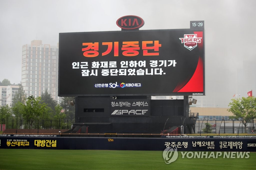 The scoreboard at Gwangju-Kia Champions Field in Gwangju, 330 kilometers south of Seoul, flashes a message on the suspension of the Korea Baseball Organization season opening game between the Kia Tigers and the Kiwoom Heroes, with black smoke from a fire near the stadium covering the field. (Yonhap)