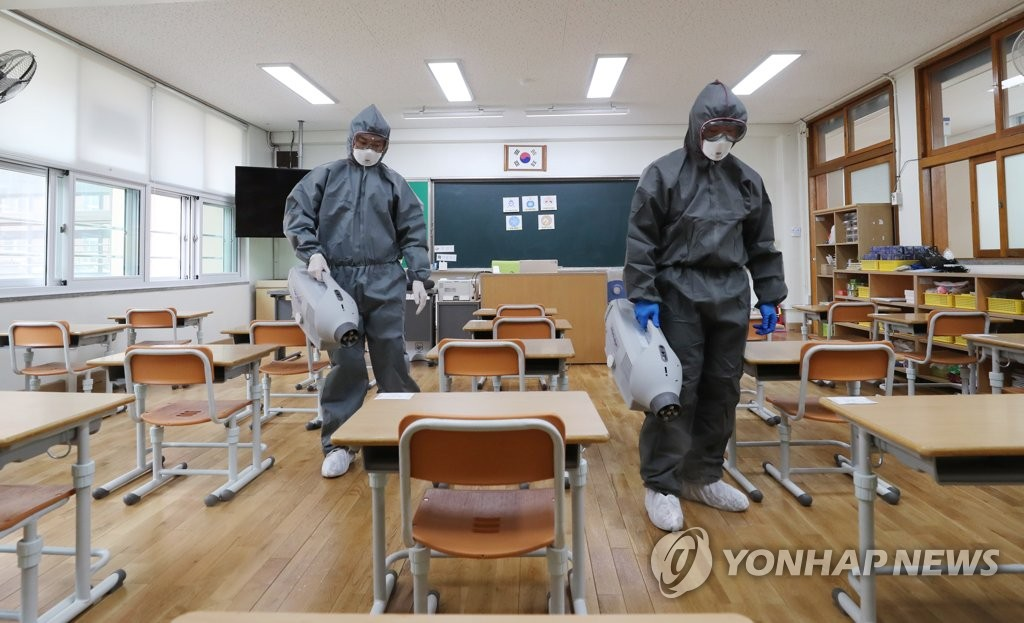 Health workers disinfect a classroom at an elementary school in Gwangju on May 26, 2020, one day ahead of school reopening. (Yonhap)
