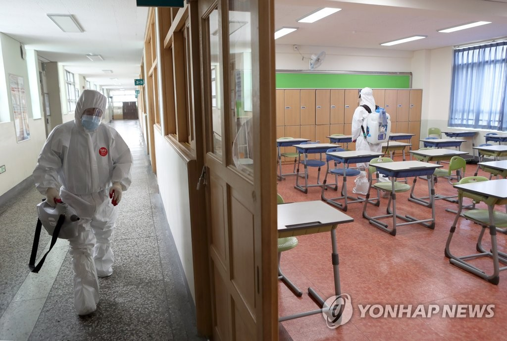 Health workers disinfect a classroom at a high school in the southeastern port city of Busan on May 30, 2020, after a senior at the school tested positive for the new coronavirus earlier this week. (Yonhap)