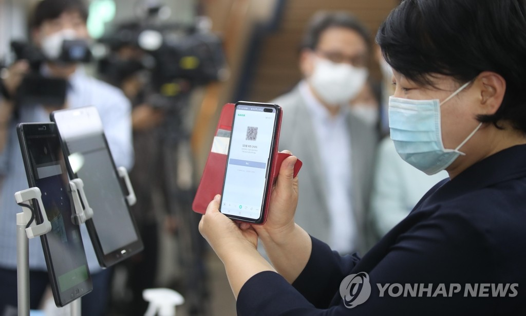 A churchgoer scans her quick-response (QR) code with a smartphone before entering a church in central Seoul on June 2, 2020. (Yonhap)