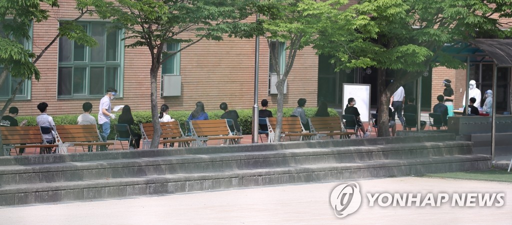 Students and teachers of a high school in northern Seoul wait in line to be tested for the new coronavirus at a makeshift clinic on June 8, 2020, after one of its students tested positive for the virus a day earlier. (Yonhap)