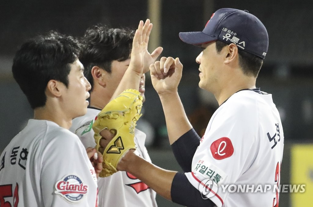 Lotte Giants' starter Noh Kyung-eun (R) is greeted by teammates after completing the top of the seventh inning of a Korea Baseball Organization regular season game against the Hanwha Eagles at Sajik Stadium in Busan, 450 kilometers southeast of Seoul. (Yonhap)