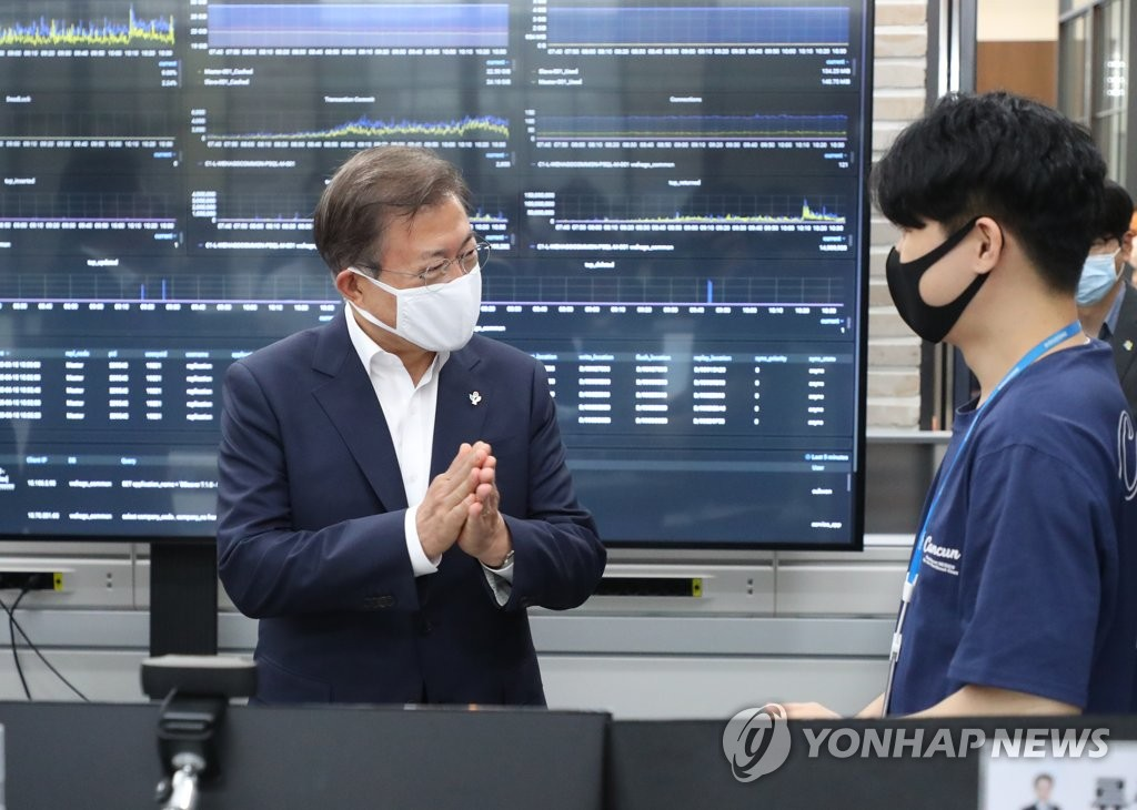 President Moon Jae-in (L) talks with employees at the Gangchon Campus of DUZON Bizon Co. in Gangwon Province on June 18, 2020. (Yonhap)
