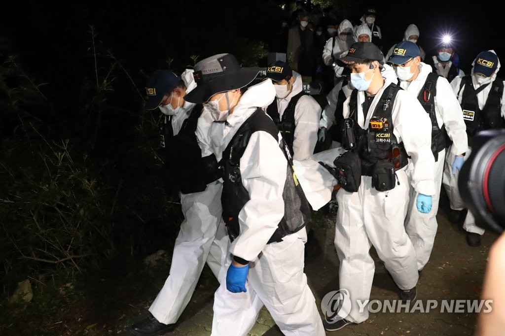 Police scientific investigation team members carry the body of Seoul Mayor Park Won-soon, who was found dead in the forested hills of Mount Bukak in Seoul on July 10, 2020. (Yonhap)