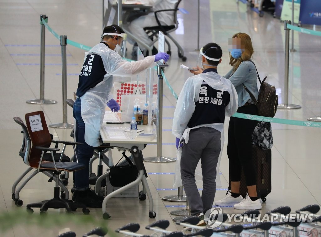 Health workers speak with a tourist at Incheon International Airport in Incheon on July 17, 2020. (Yonhap)