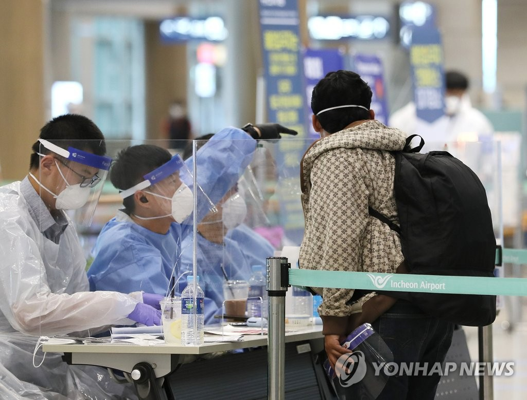 Health officials give instructions to arrivals at Incheon International Airport in Incheon, west of Seoul, on July 20, 2020. (Yonhap)