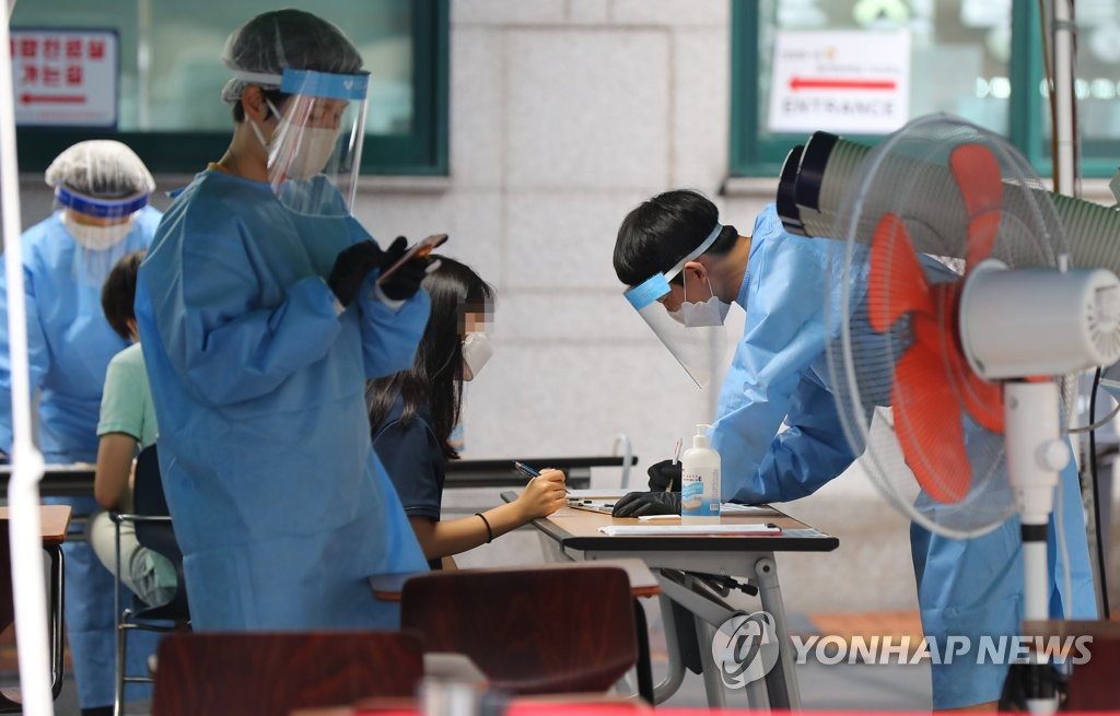 Medical workers carry out new coronavirus tests on visitors at a makeshift clinic located in southern Seoul on July 23, 2020. (Yonhap)