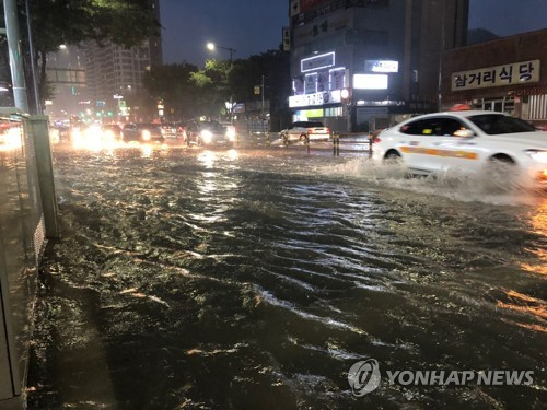 Cars plow through partially flooded roads in Busan