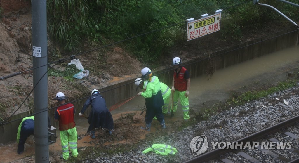 Train officials work to restore a rain-damaged railway in North Jeolla Province on Aug. 8, 2020. (Yonhap)