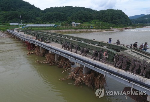 Soldiers build makeshift bridge for flood-affected residents