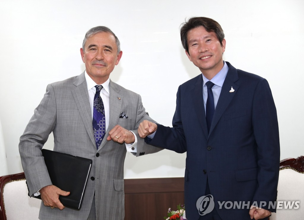 Unification Minister Lee In-young (R), South Korea's point man for inter-Korean relations, bumps elbows with U.S. Ambassador to South Korea Harry Harris during their meeting at Lee's office in Seoul on Aug. 18, 2020. (Yonhap)