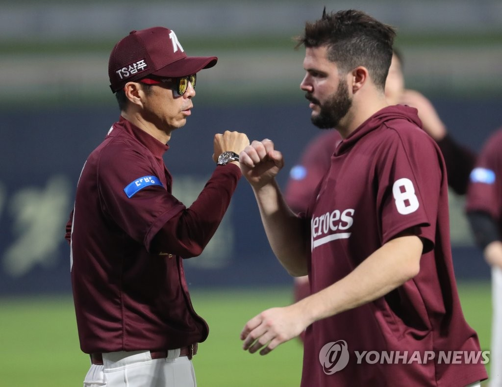 In this file photo from Aug. 19, 2020, Kiwoom Heroes' manager Son Hyuk (L) bumps fists with his starting pitcher Jake Brigham after the Heroes' 6-4 win over the NC Dinos in a Korea Baseball Organization regular season game at Changwon NC Park in Changwon, 400 kilometers southeast of Seoul. (Yonhap)