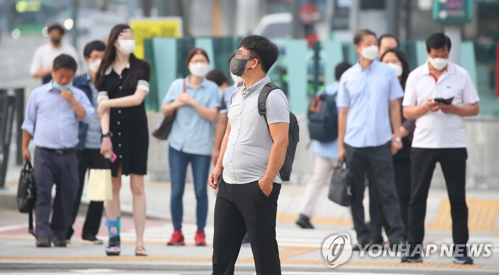 Commuters wearing protective masks wait at a pedestrian crossing in central Seoul on Aug. 25, 2020. (Yonhap)
