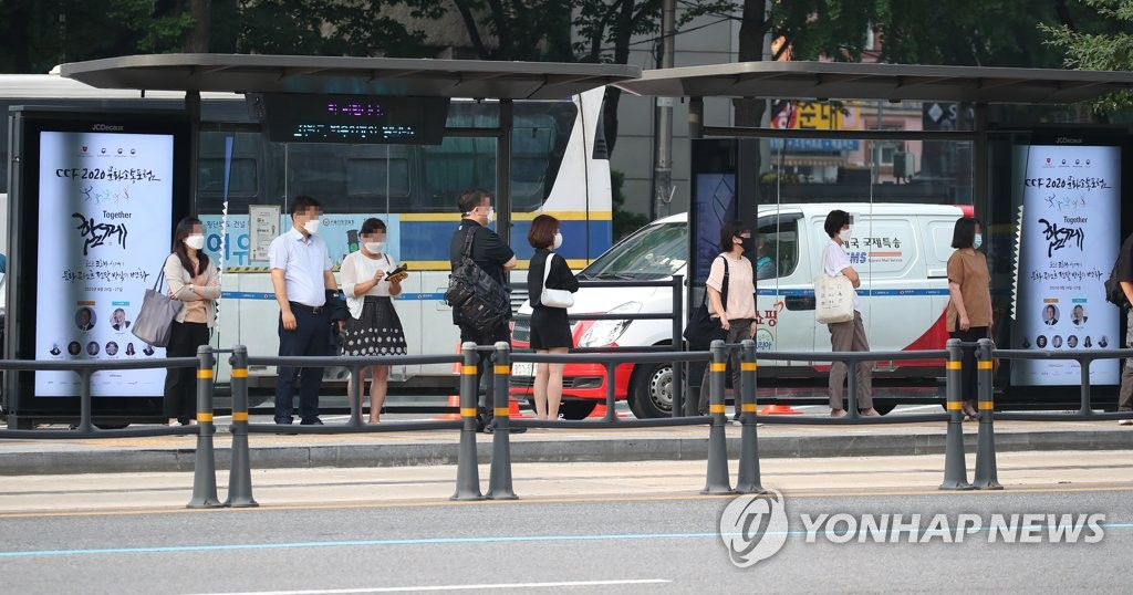 Citizens wait for buses while keeping social distancing at a bus stop in Seoul on Aug. 25, 2020, the second day of obligatory wearing of masks indoors and outdoors in the capital city amid the resurgence of COVID-19 nationwide. (Yonhap)