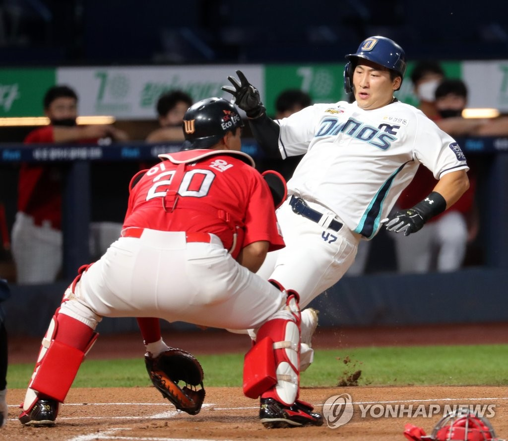 In this file photo from Aug. 30, 2020, Na Sung-bum of the NC Dinos (R) scores a run against the SK Wyverns in a Korea Baseball Organization regular season game at Changwon NC Park in Changwon, 400 kilometers southeast of Seoul. (Yonhap)