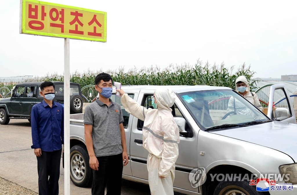 In this undated photo released by the North's official Korean Central News Agency on Sept. 4, 2020, body temperature checks are carried out on people in Pyongyang amid the coronavirus pandemic. (For Use Only in the Republic of Korea. No Redistribution) (Yonhap)