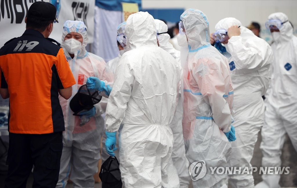 This file photo, taken on Sept. 16, 2020, shows firefighters clad in protective gear preparing for a virus patient transport training program in Daegu. (Yonhap)