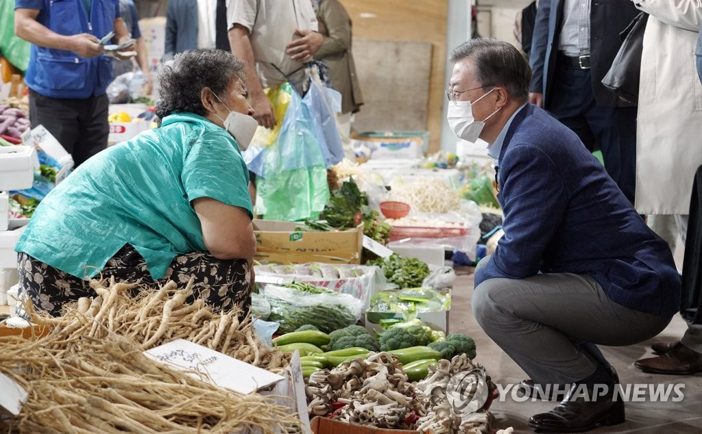 President Moon Jae-in (R) talks with a merchant at the Inwang traditional market in western Seoul on Sept. 29, 2020, in this photo provided by Cheong Wa Dae. (PHOTO NOT FOR SALE) (Yonhap)