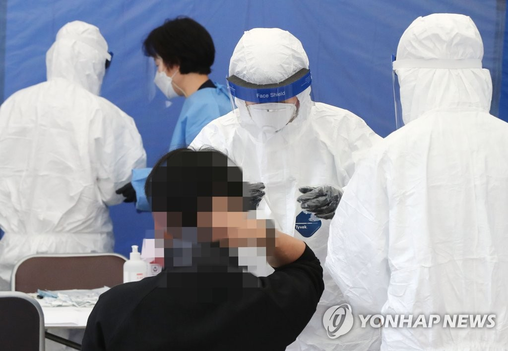 Medical workers carry out new coronavirus tests at a makeshift clinic located in southern Seoul on Oct. 21, 2020. (Yonhap)