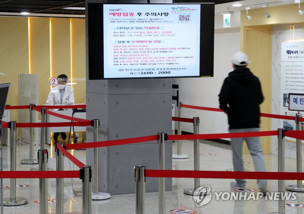 This photo, taken on Oct. 23, 2020, shows a man approaching a doctor to receive a flu shot at a hospital in western Seoul as public fear grows over a possible link between vaccines and recent deaths.