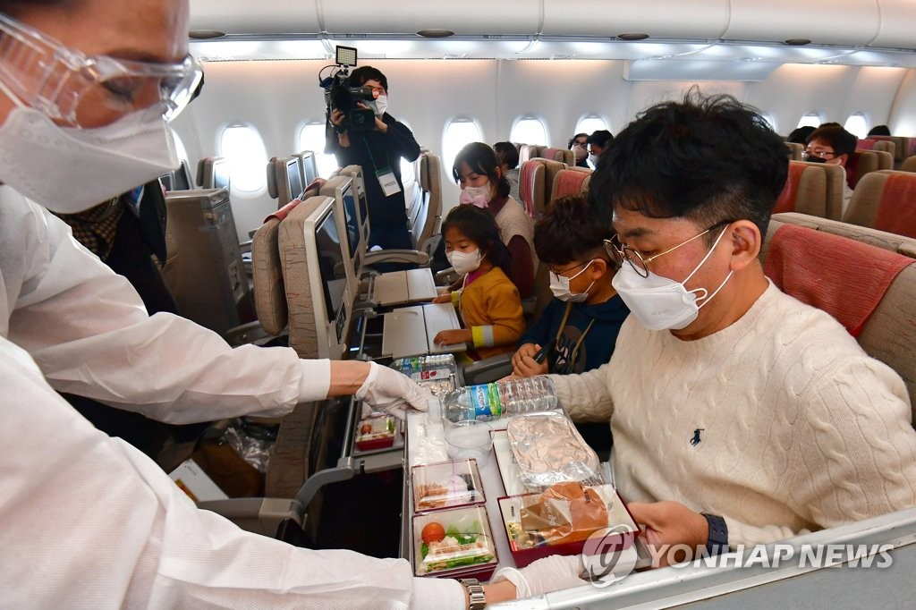 This photo, provided by the Incheon International Airport press pool, shows a flight attendant serving an in-flight meal on an Asiana Airlines flight to nowhere on Oct. 24, 2020. (Yonhap)