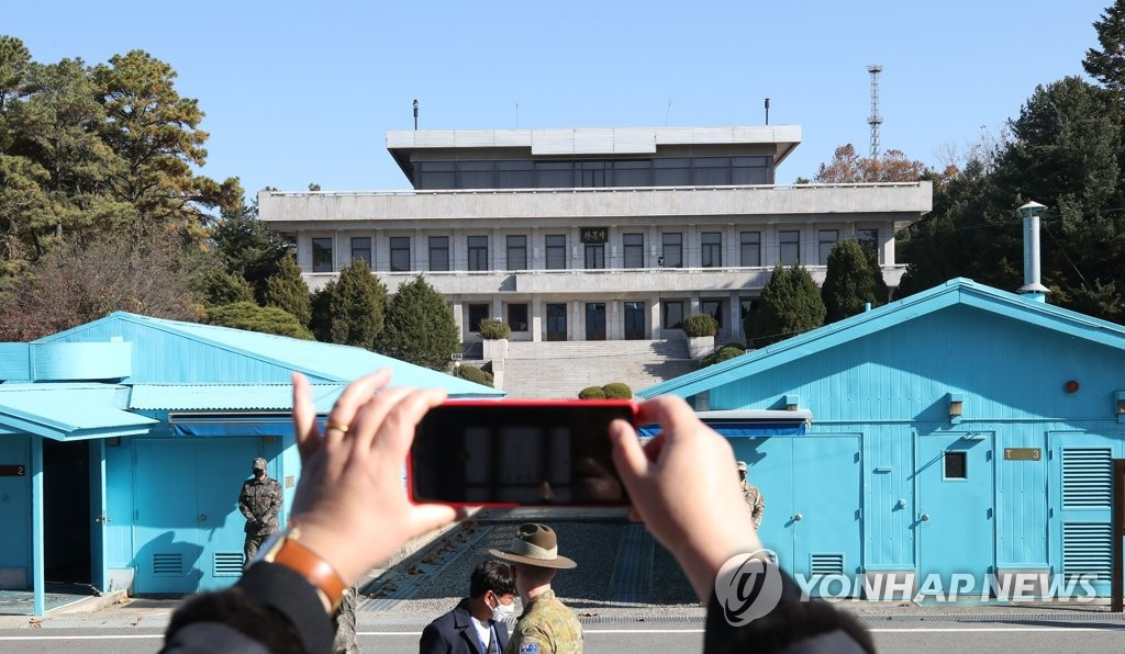 In this file photo taken by Joint Press Corps on Nov. 4, 2020, a member of a demonstration tour group takes a photo at the inter-Korean truce village of Panmunjom, north of Seoul. (PHOTO NOT FOR SALE) (Yonhap)