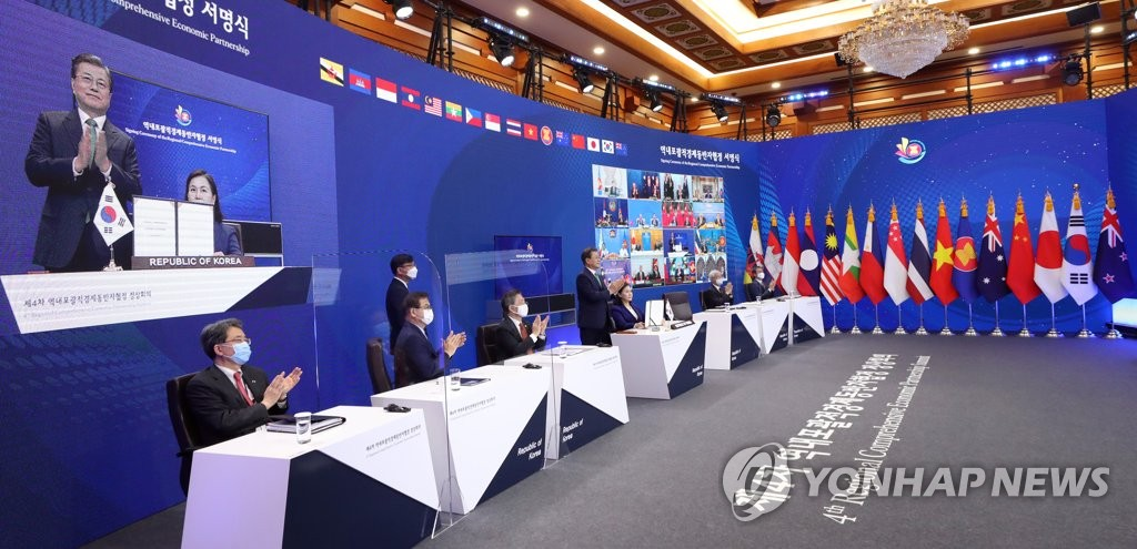 South Korean President Moon Jae-in, shown on a screen (L), attends the signing ceremony of the Regional Comprehensive Economic Partnership (RCEP), held via video links, at Cheong Wa Dae in Seoul on Nov. 15, 2020. (Yonhap)