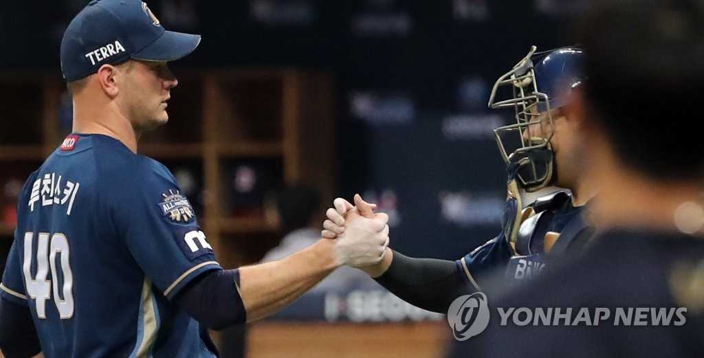 NC Dinos' pitcher Drew Rucinski (L) shakes hands with catcher Yang Eui-ji after closing out a 3-0 victory over the Doosan Bears in Game 4 of the Korean Series at Gocheok Sky Dome in Seoul on Nov. 21, 2020. (Yonhap)