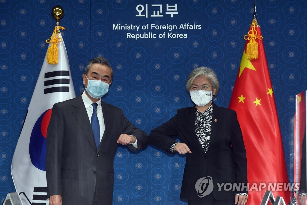 Foreign Minister Kang Kyung-wha (R) and Chinese Foreign Minister Wang Yi bump elbows before their talks at the foreign ministry in Seoul on Nov. 26, 2020. (Pool photo) (Yonhap)