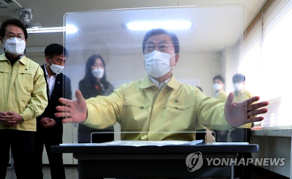 President Moon Jae-in checks a plastic divider at Osan High School in Seoul on Nov. 29, 2020. (Yonhap)