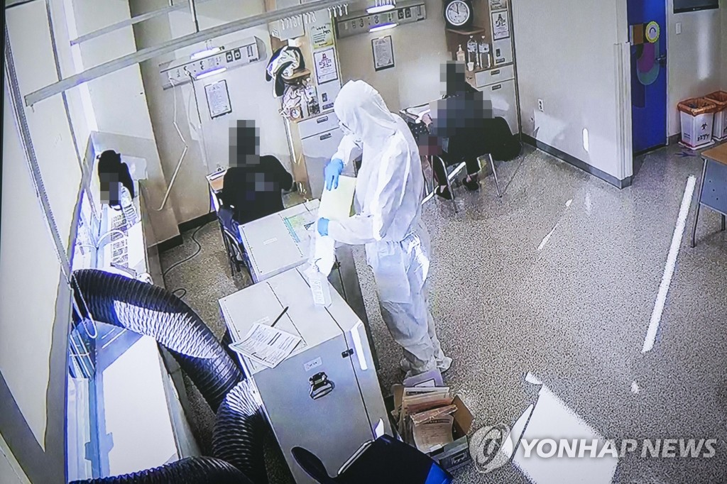 This footage from a closed circuit TV shows two students who have tested positive for the coronavirus taking the College Scholastic Ability Test at Seoul Medical Center on Dec. 3, 2020. (POOL PHOTO) (Yonhap)