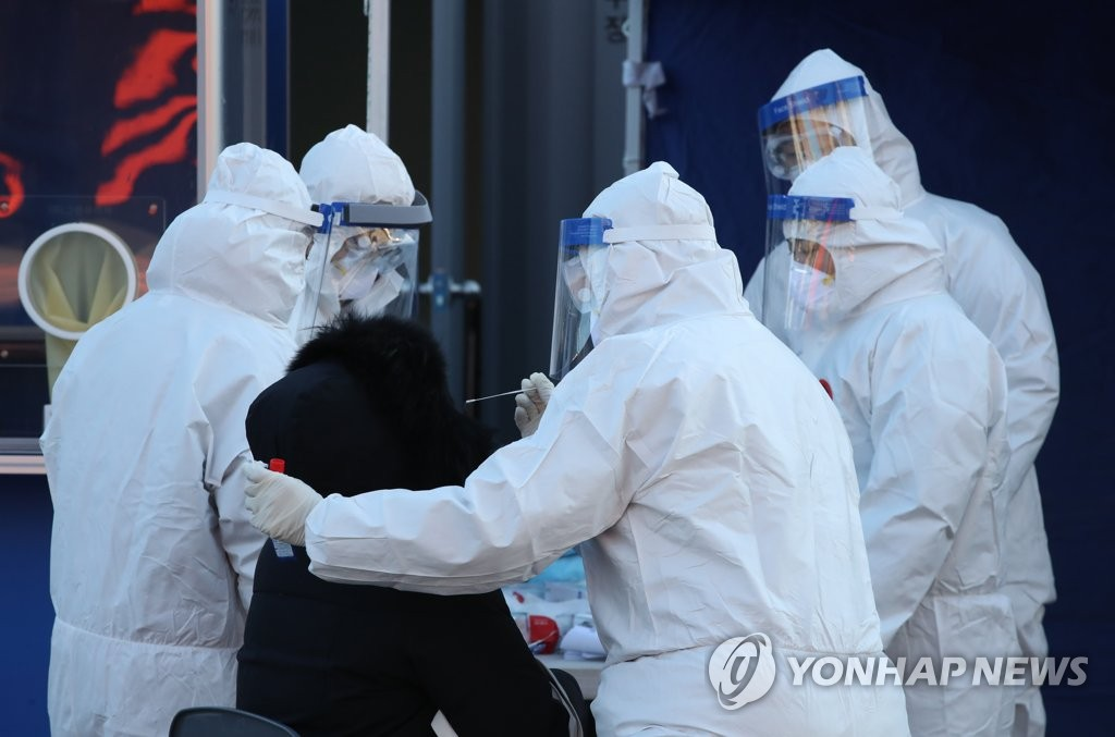 A visitor receives a COVID-19 test at a makeshift clinic in central Seoul on Dec. 14, 2020. (Yonhap)