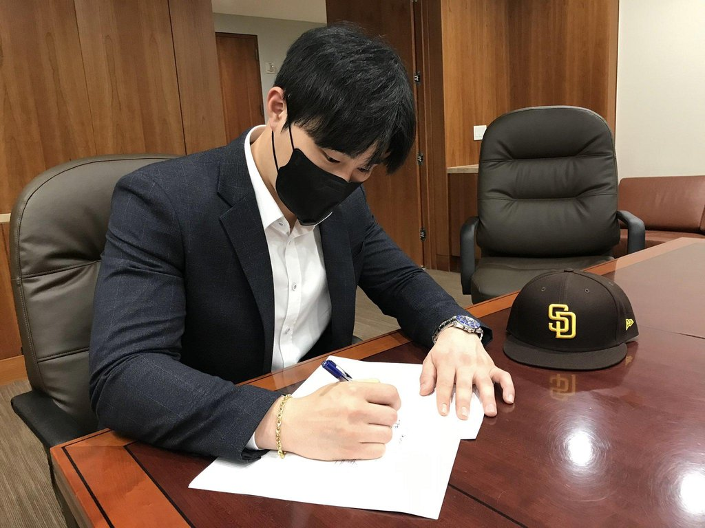 This image captured from the Twitter page of the San Diego Padres on Jan. 1, 2021, shows the club's new South Korean player, Kim Ha-seong, signing his contract. (PHOTO NOT FOR SALE) (Yonhap)