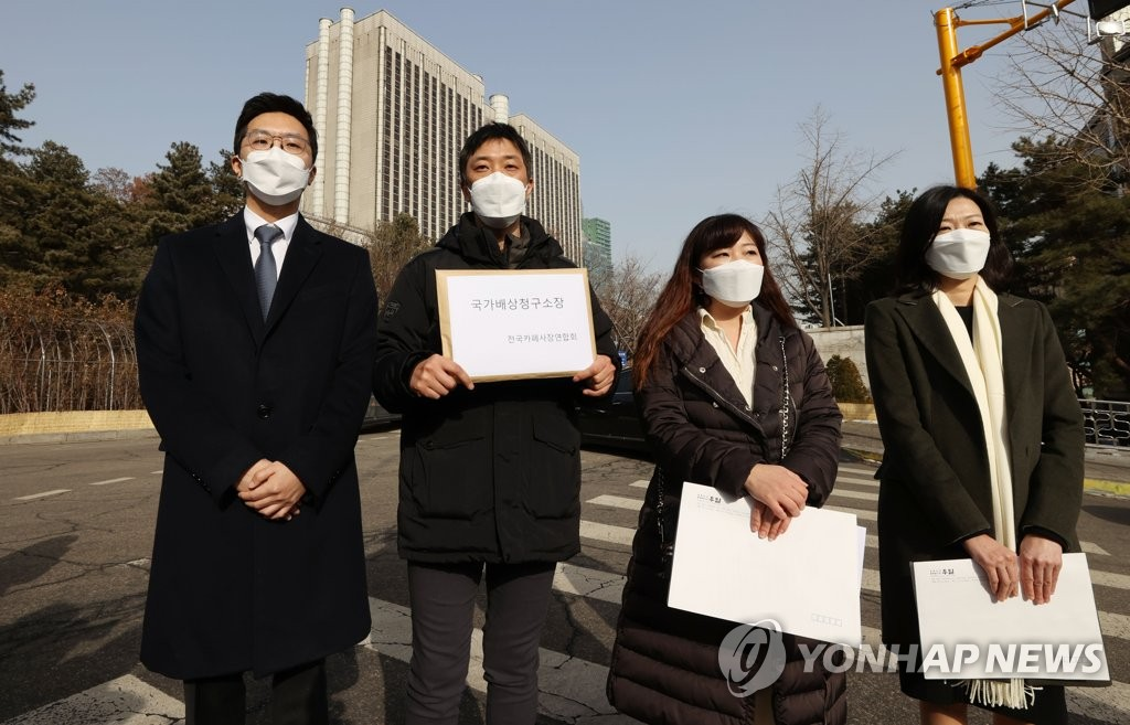 Member of a cafe owners' association hold a press conference outside the Seoul Central District Court on Jan. 14, 2021, before filing a damage suit against the government at the court. (Yonhap)
