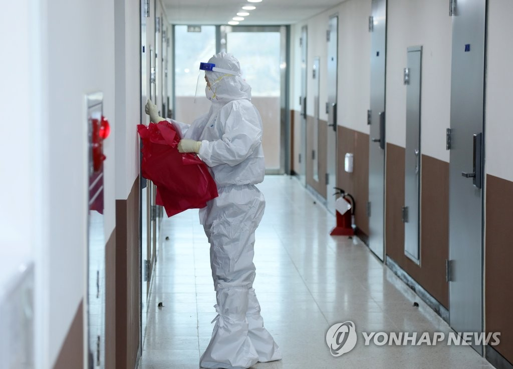 This photo taken on Jan. 21, 2021, shows a health worker clad in a protective suit checking a dormitory at the Joongbu University campus in Goyang, north of Seoul, that is being used as a temporary shelter for arrivals from overseas. (Yonhap)